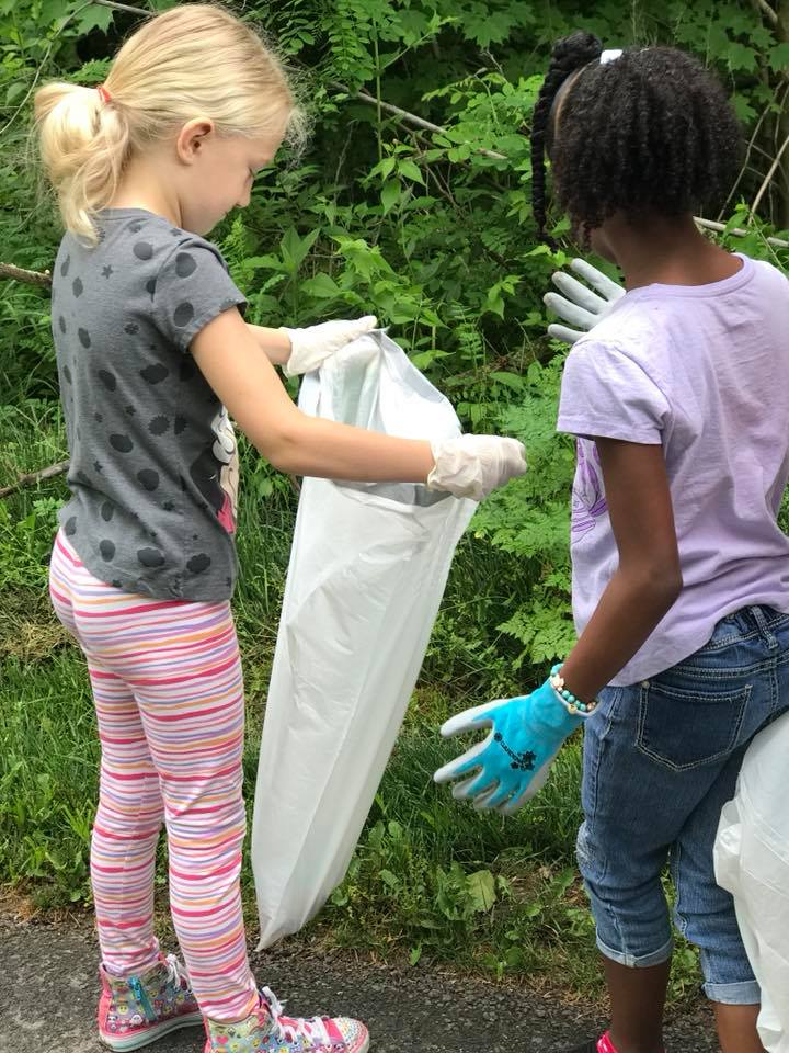 little girls cleaning up trash