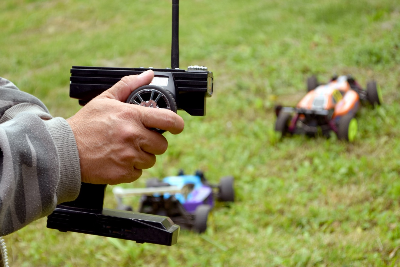 a close up of a hand holding a remote control for RC cars