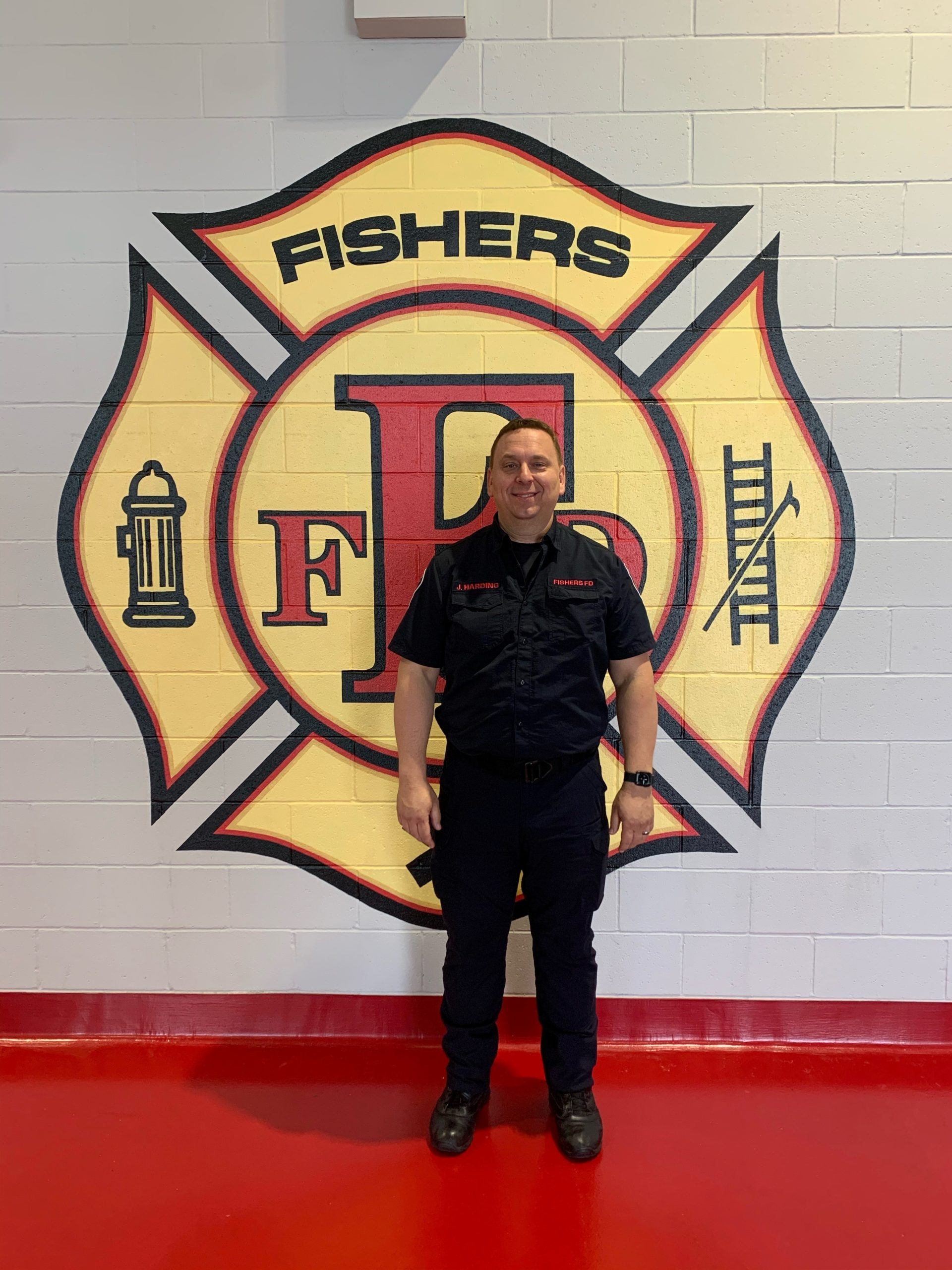 joe harding standing in front of the fishers fire department logo