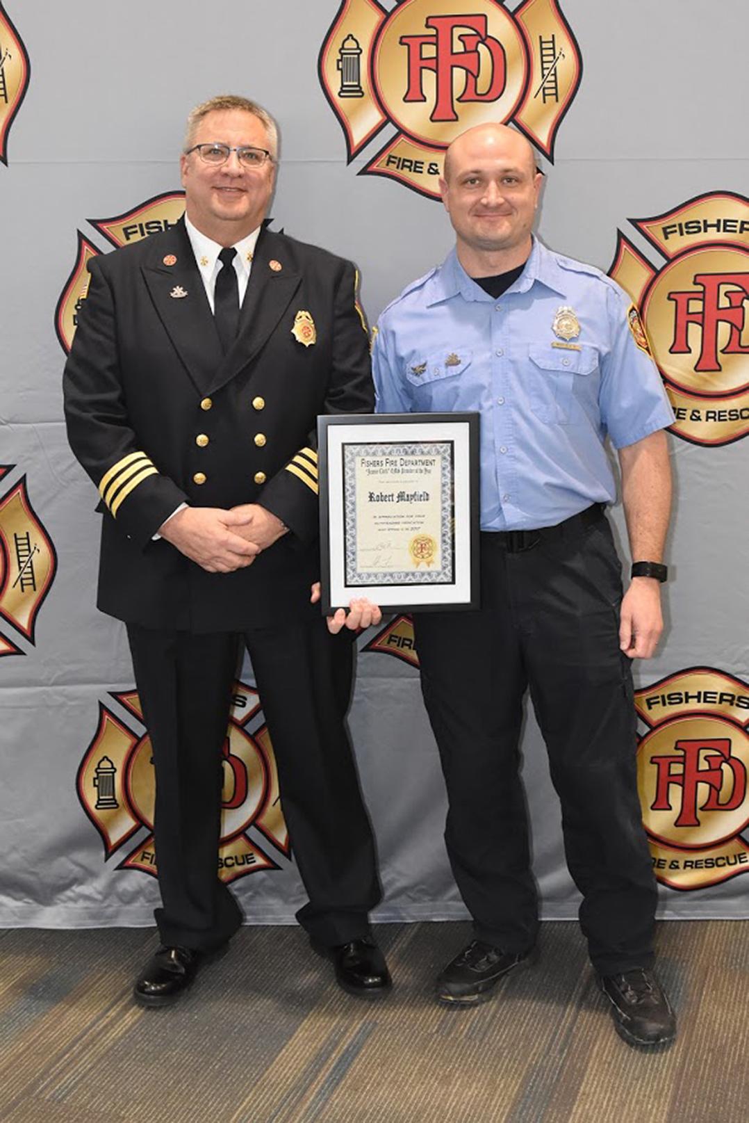 robert mayfield getting an award from another firefighter