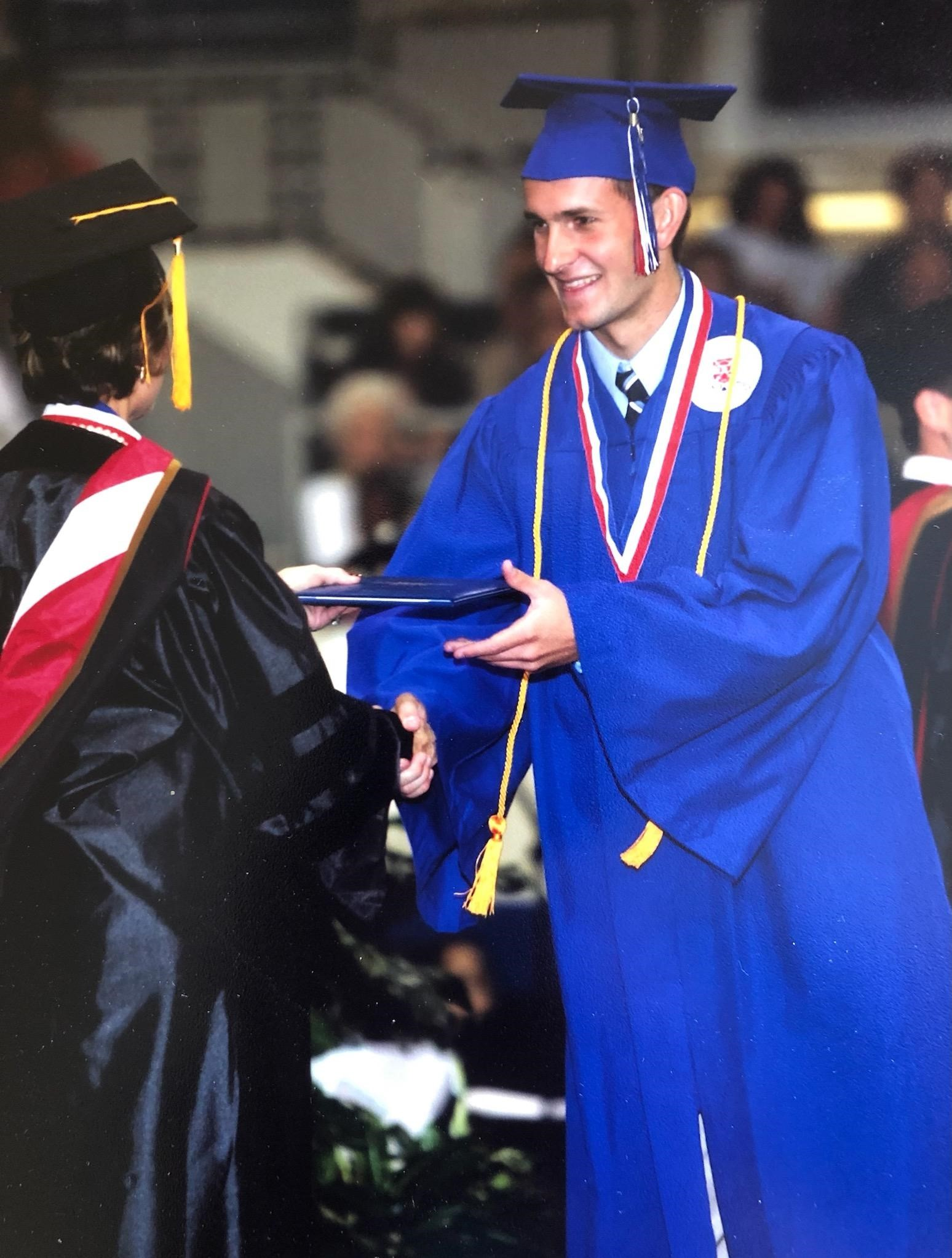 scott spillman in his cap and gown receiving his diploma at his high school graduation