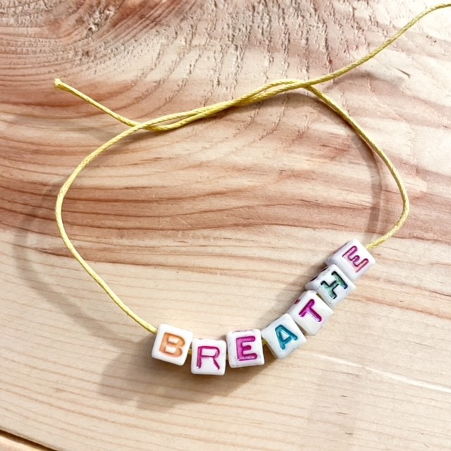 a string bracelet with beads that say breathe