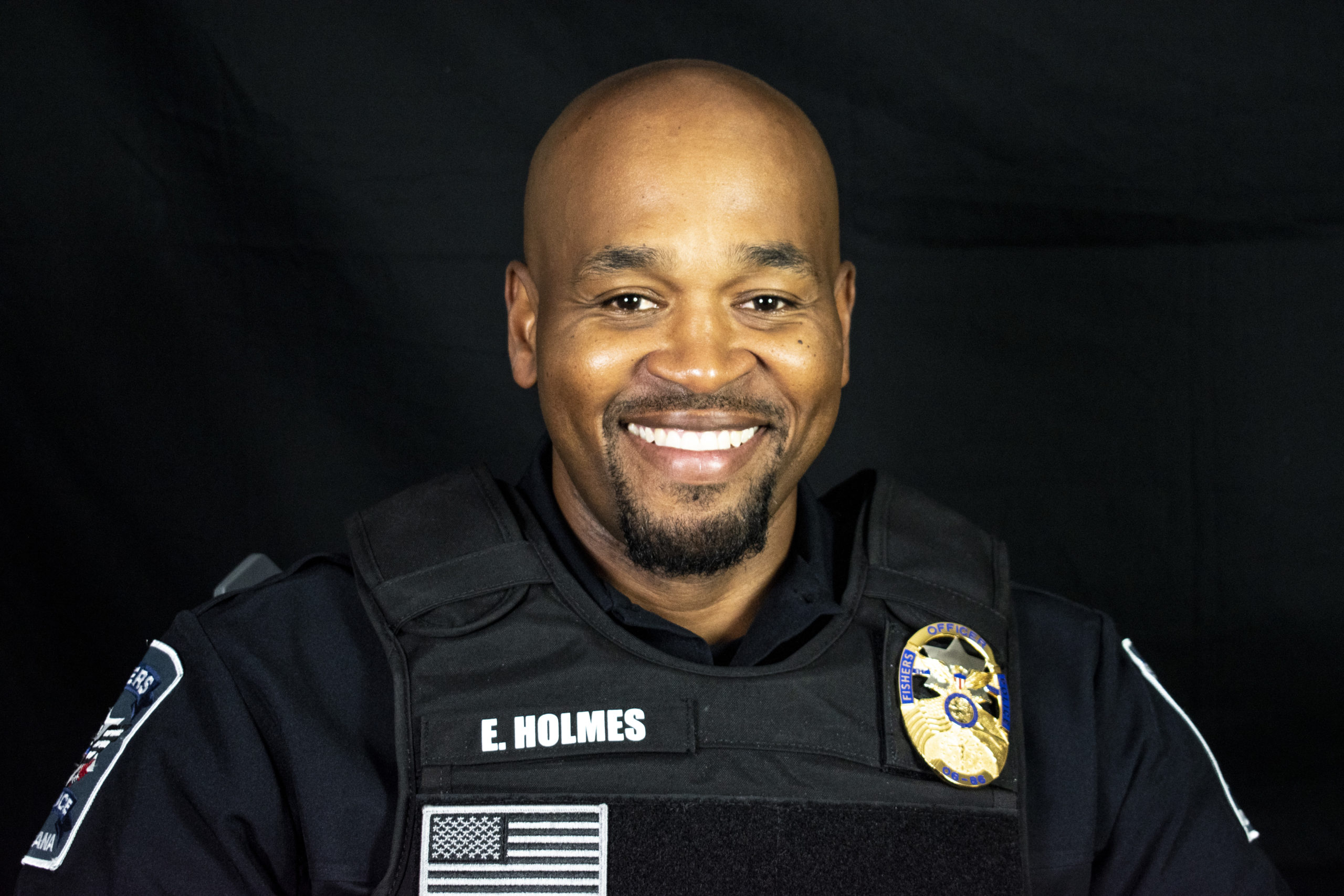 a headshot of a man in a police uniform smiling