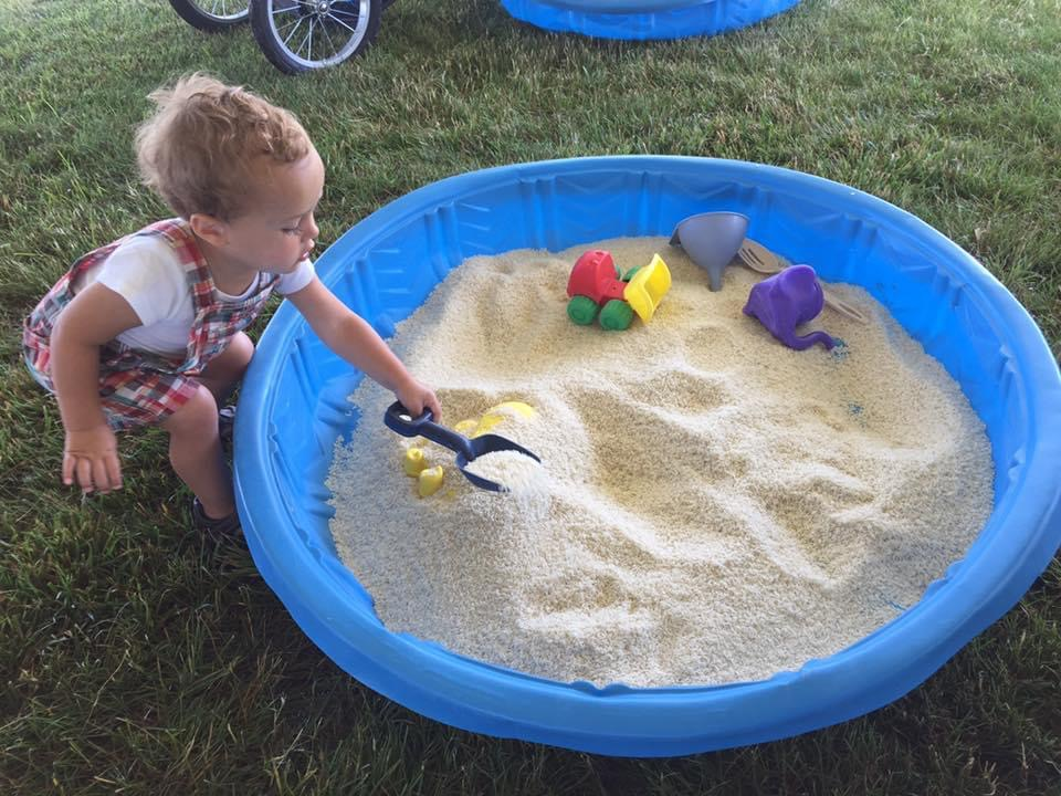 a kid playing in a kiddie pool filled with sand