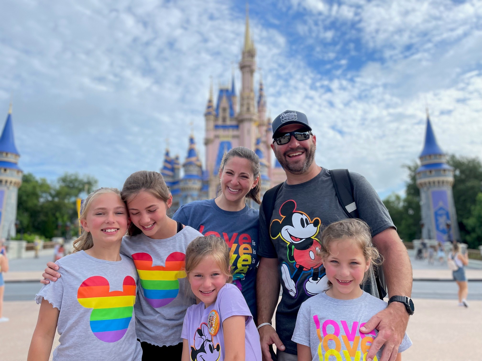 a mom and dad with their four daughters standing in front of the castle at disney