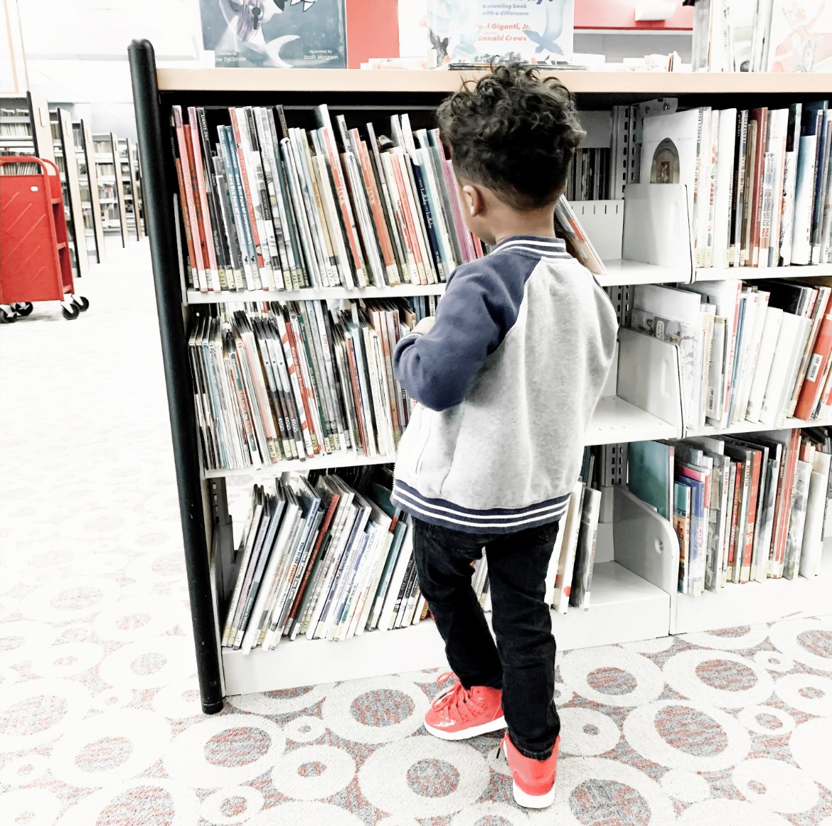 a kid standing in front of books