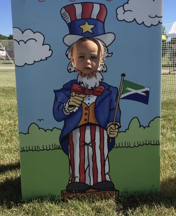 a young boy with his head in a cutout of uncle sam