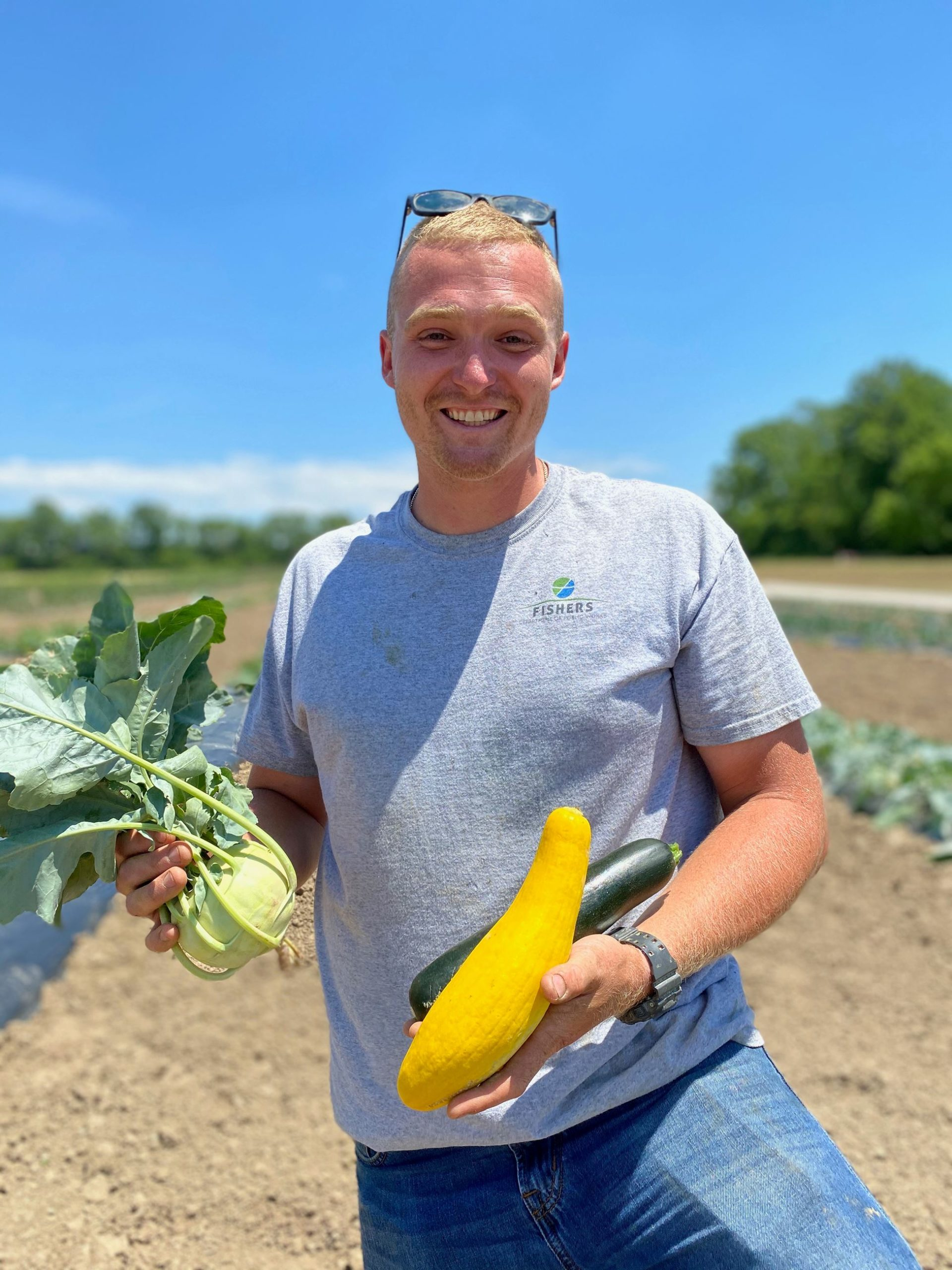 a man smiling on a farm and holding produce
