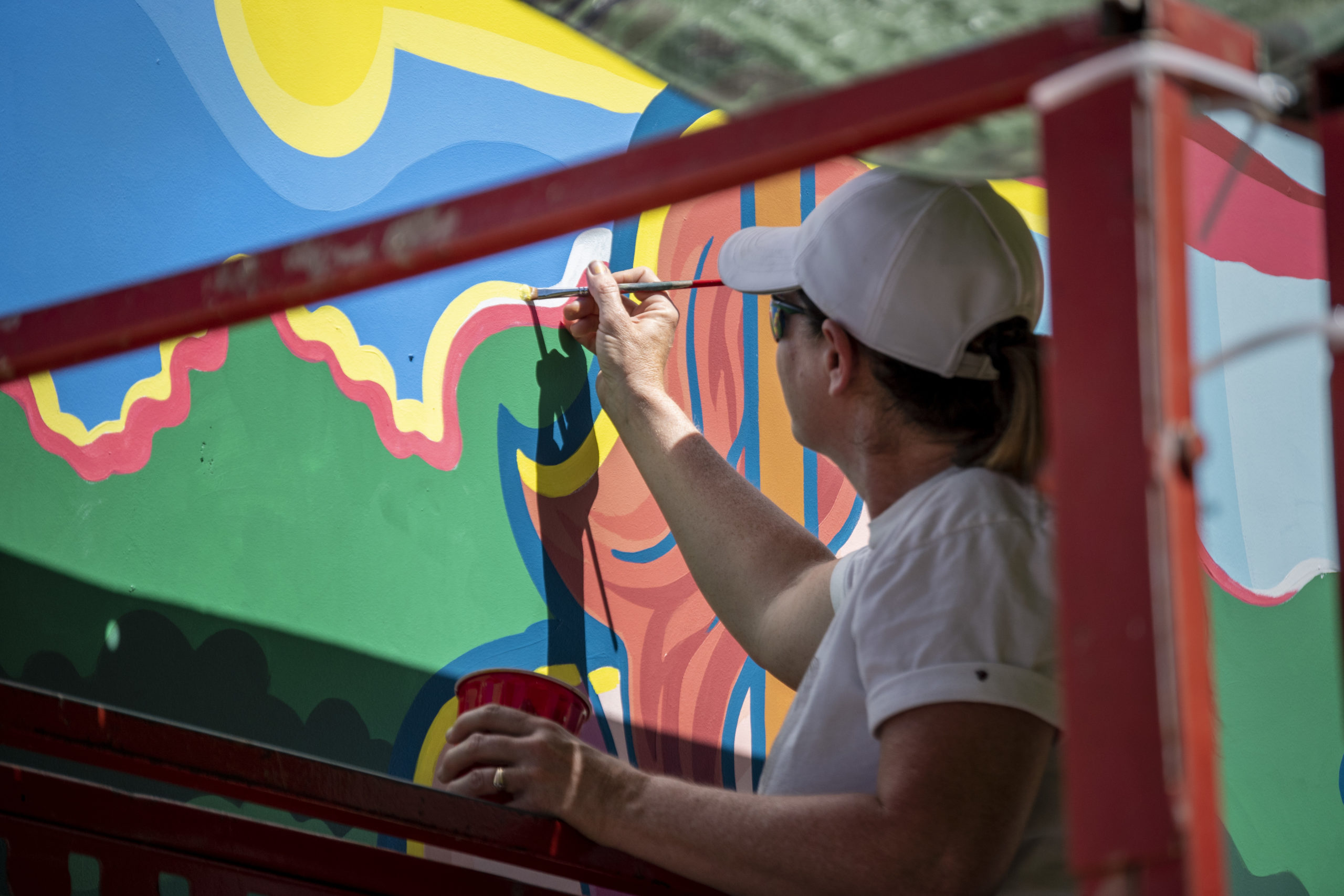 a woman working on a mural