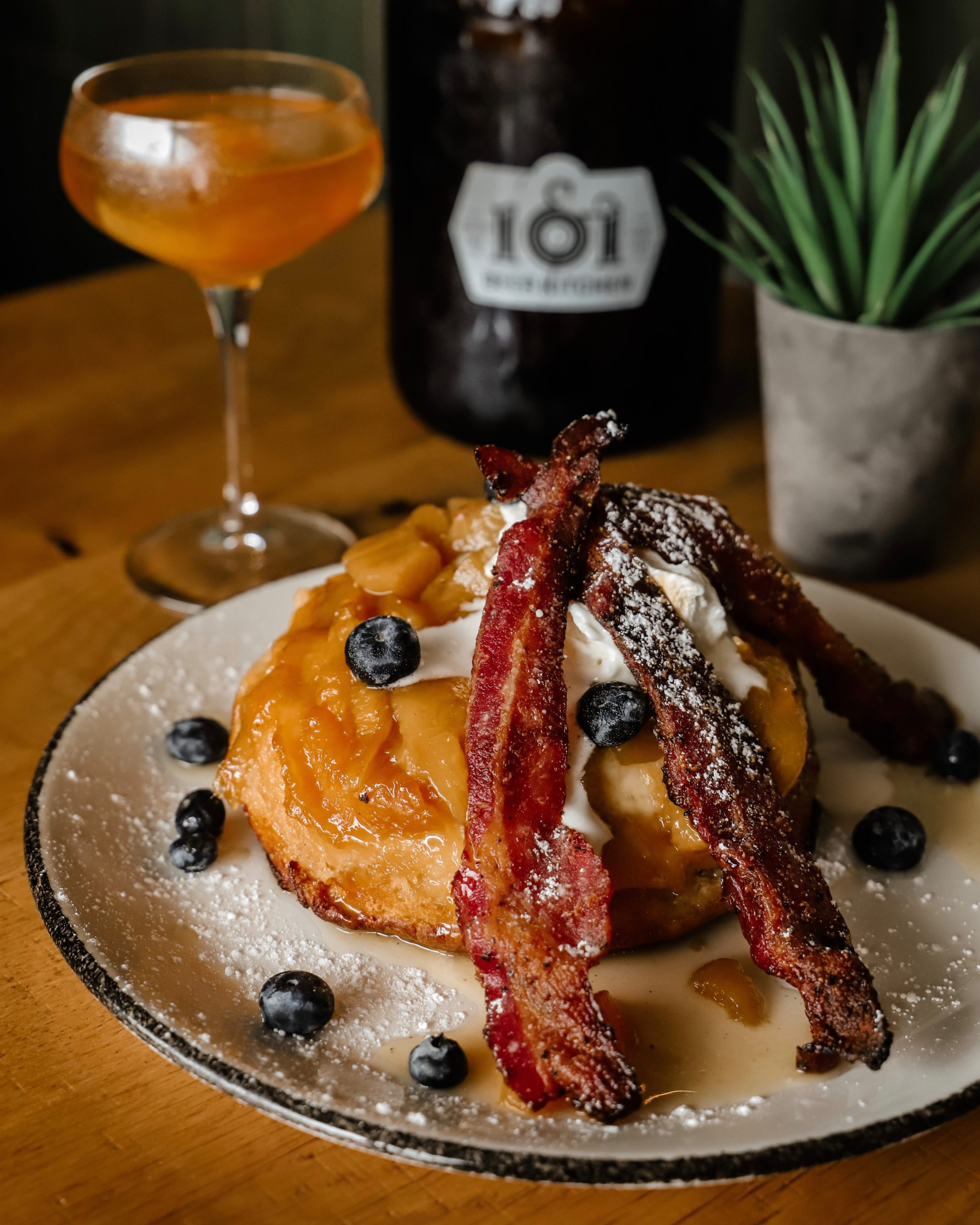 a peach pancake topped with bacon, blueberries, syrup and powdered sugar