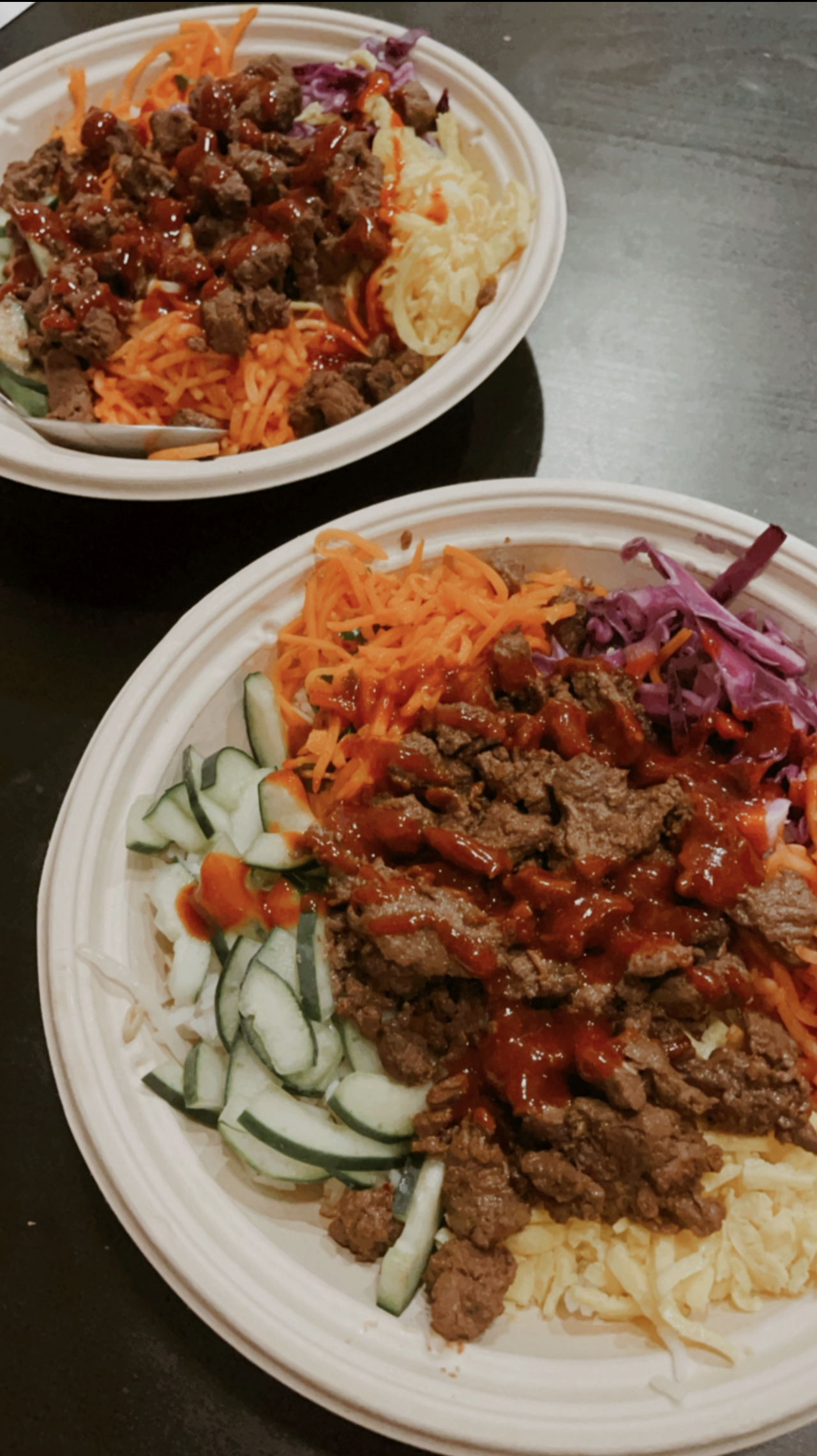 two bowls of bibimbap. they include a white rice base, topped with bean sprouts, red cabbage, cucumber, carrots, egg, kimchi and steak