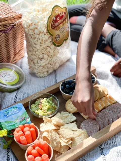 a picnic and an arm reaching down to grab food