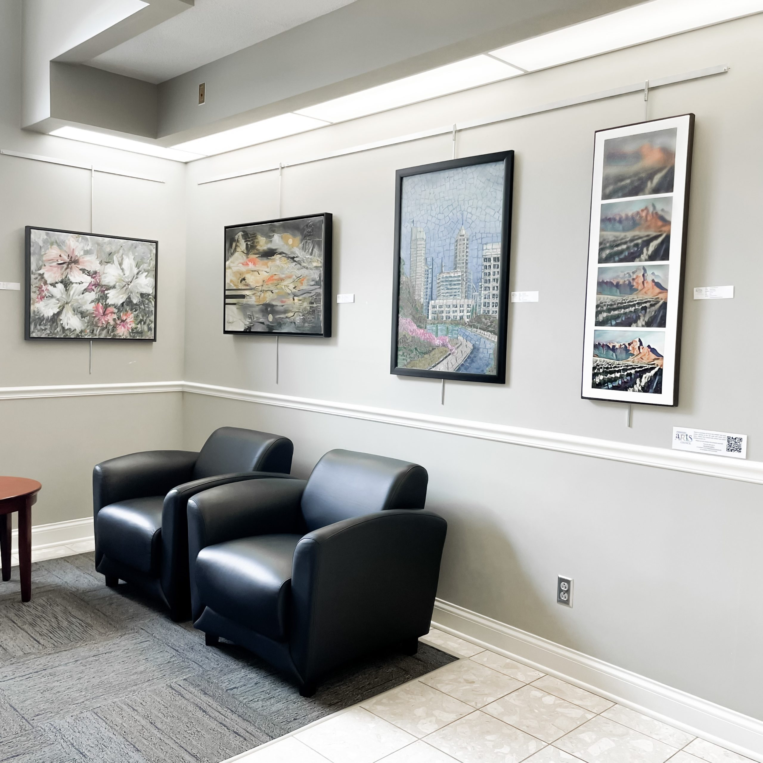 two black chairs and paintings on the wall behind them