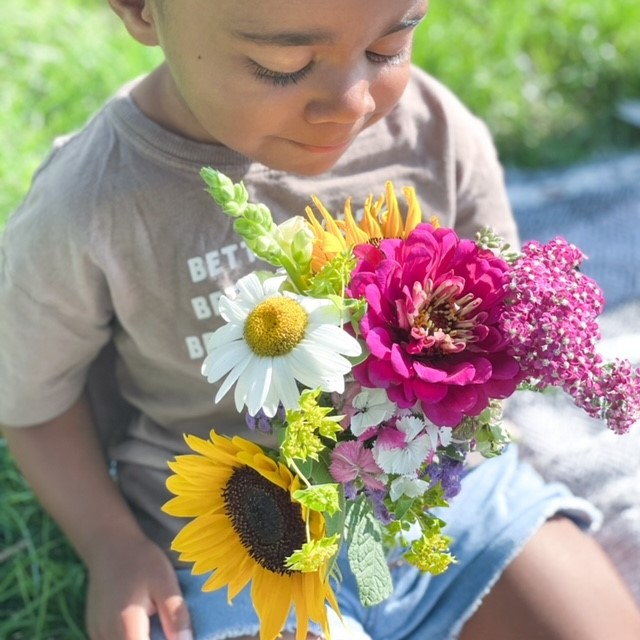 a kid holding flowers and smelling them