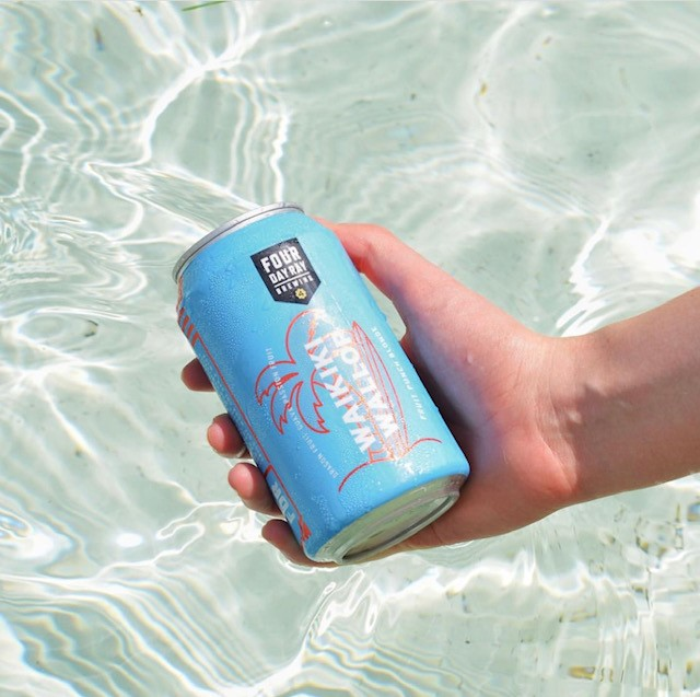 someone holding a can of beer in front of a pool