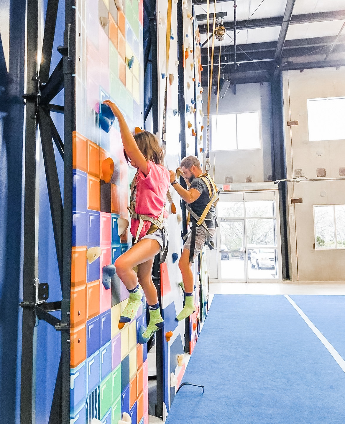 two people climbing a rock wall
