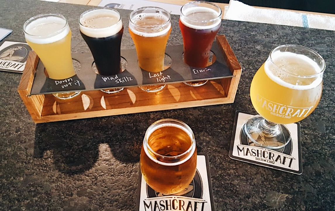 a flight of beers and two glasses of beer in front