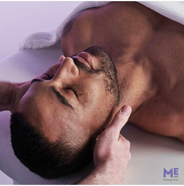 a man laying down with his eyes closed getting a massage behind his ears