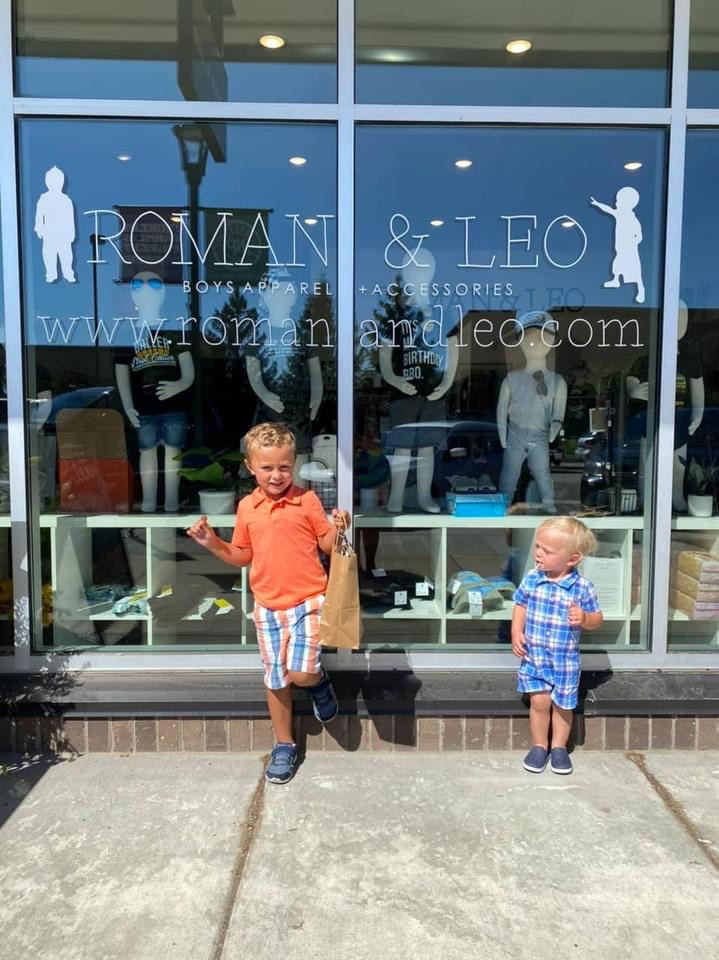 two boys standing outside of a store