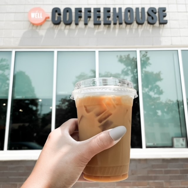 someone holding an iced coffee in front of a building