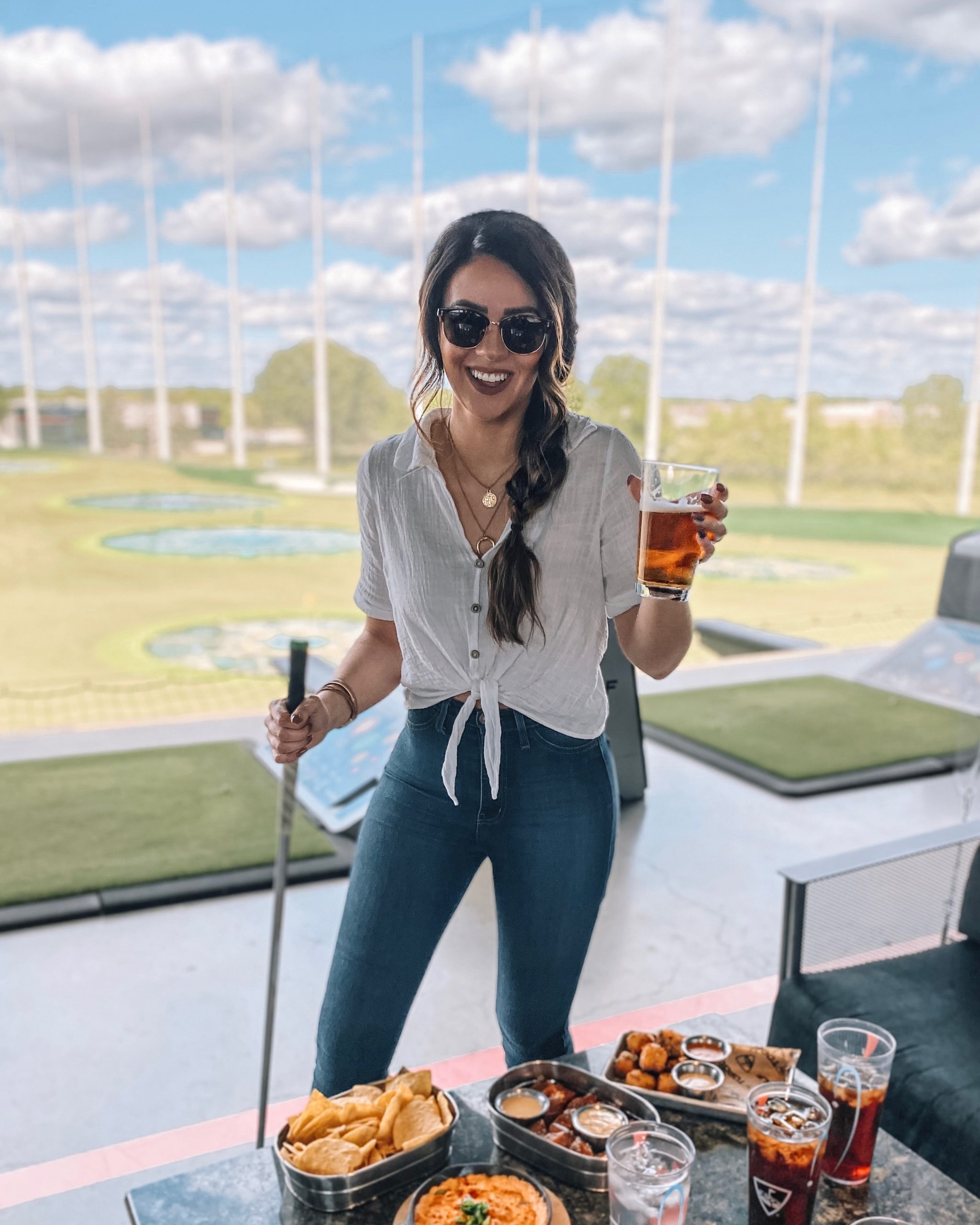 a woman smiling while holding a beer and a golf club