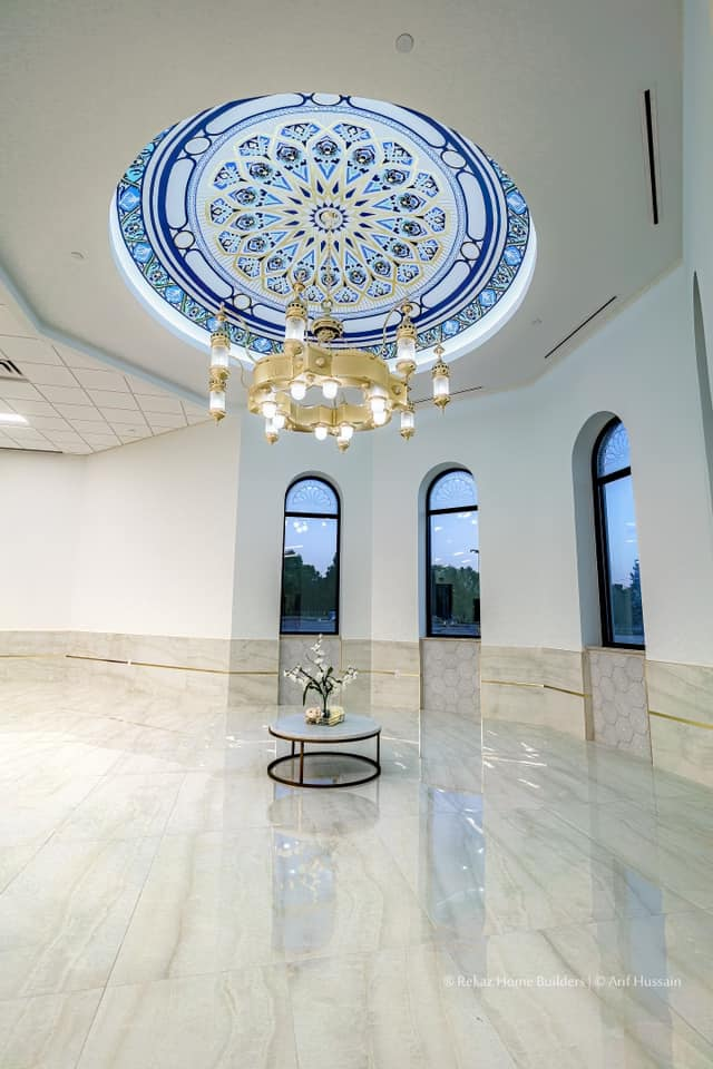 a room with white walls, light glossy wood floors, and marble etched wall. also has a decorated dome on the ceiling and hanging from the dome is a gold chandelier