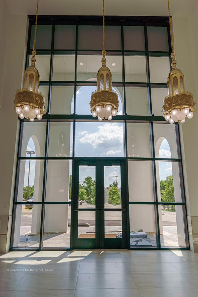 a wall of windows and three chandeliers hanging in front