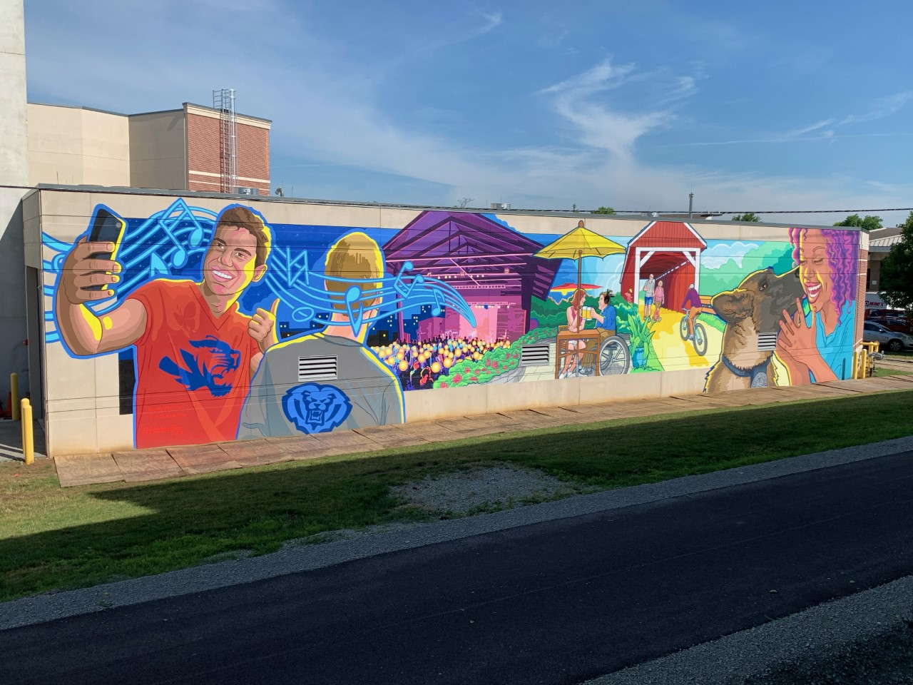 a mural of a person taking a selfie on their phone, a person with a school logo on their shirt, a concert venue with people and a covered bridge