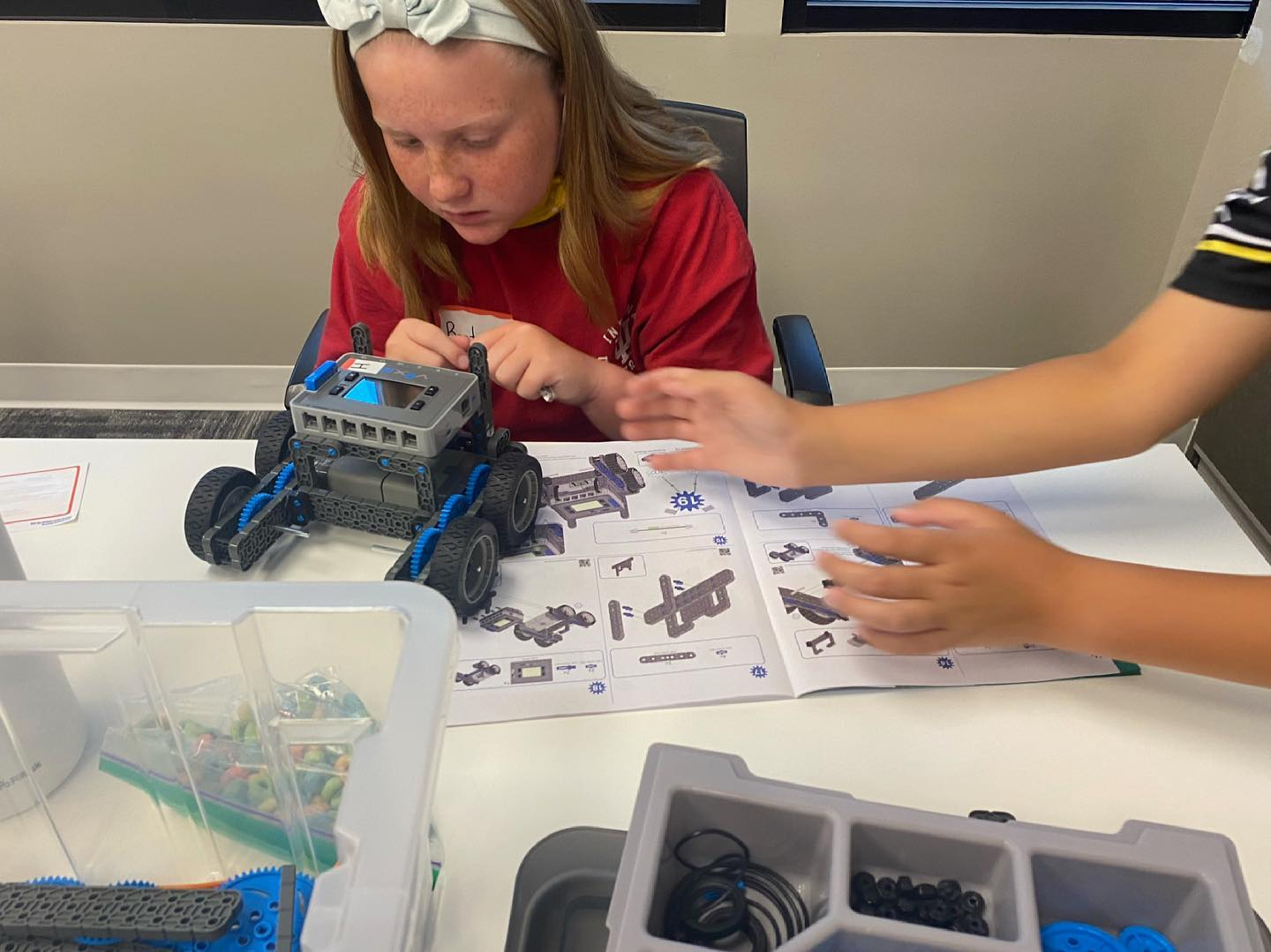 a girl building a lego car out of blue, black and grey legos