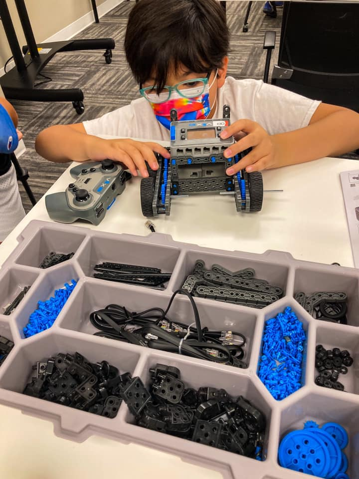 a kid sitting wearing a rainbow tie dye mask and glasses. they are building a car out of blue, grey and black legos