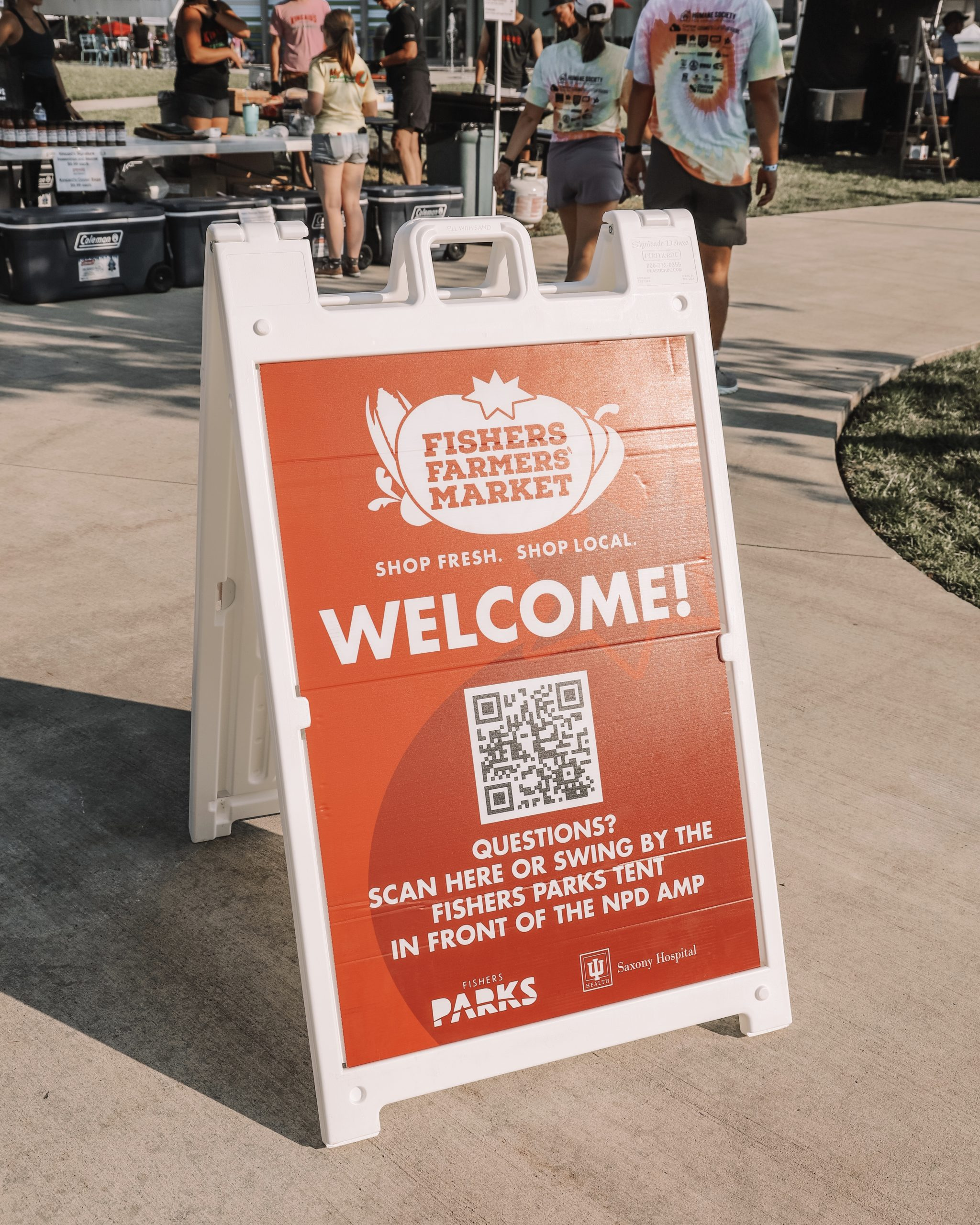 """a sign that says, """"fishers farmers market. shop fresh. shop local. welcome! questions? scan here or swing by the fishers parks tent in front of the npd amp."""""""