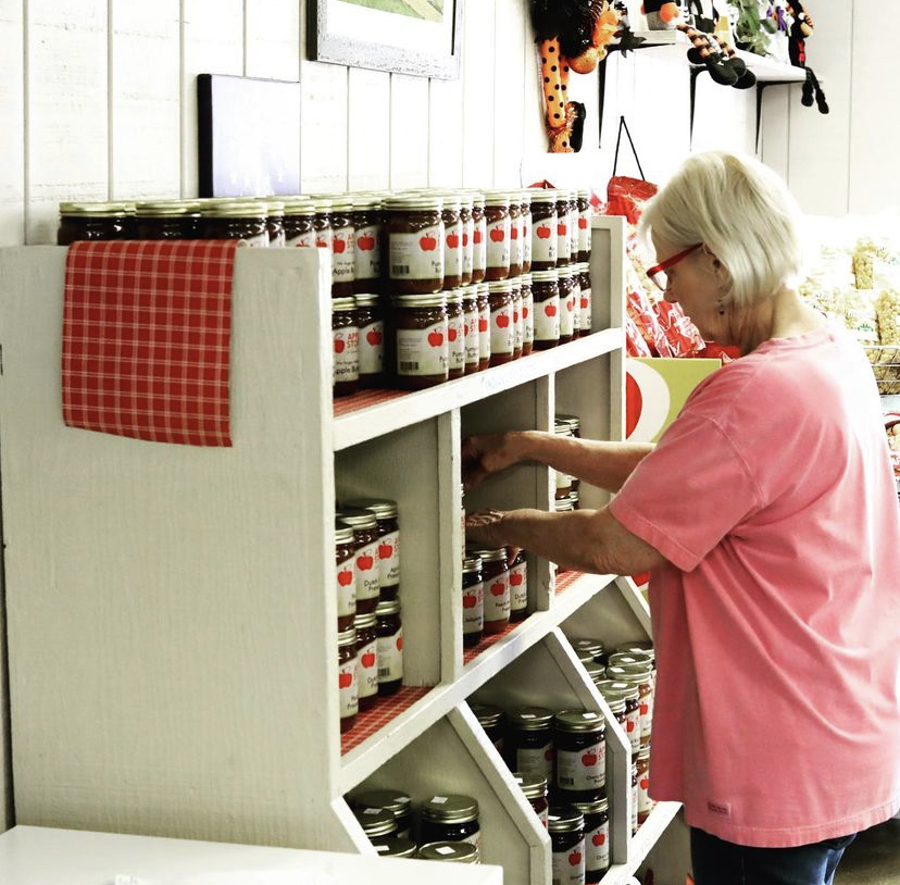 a woman organizing jars of apple butter