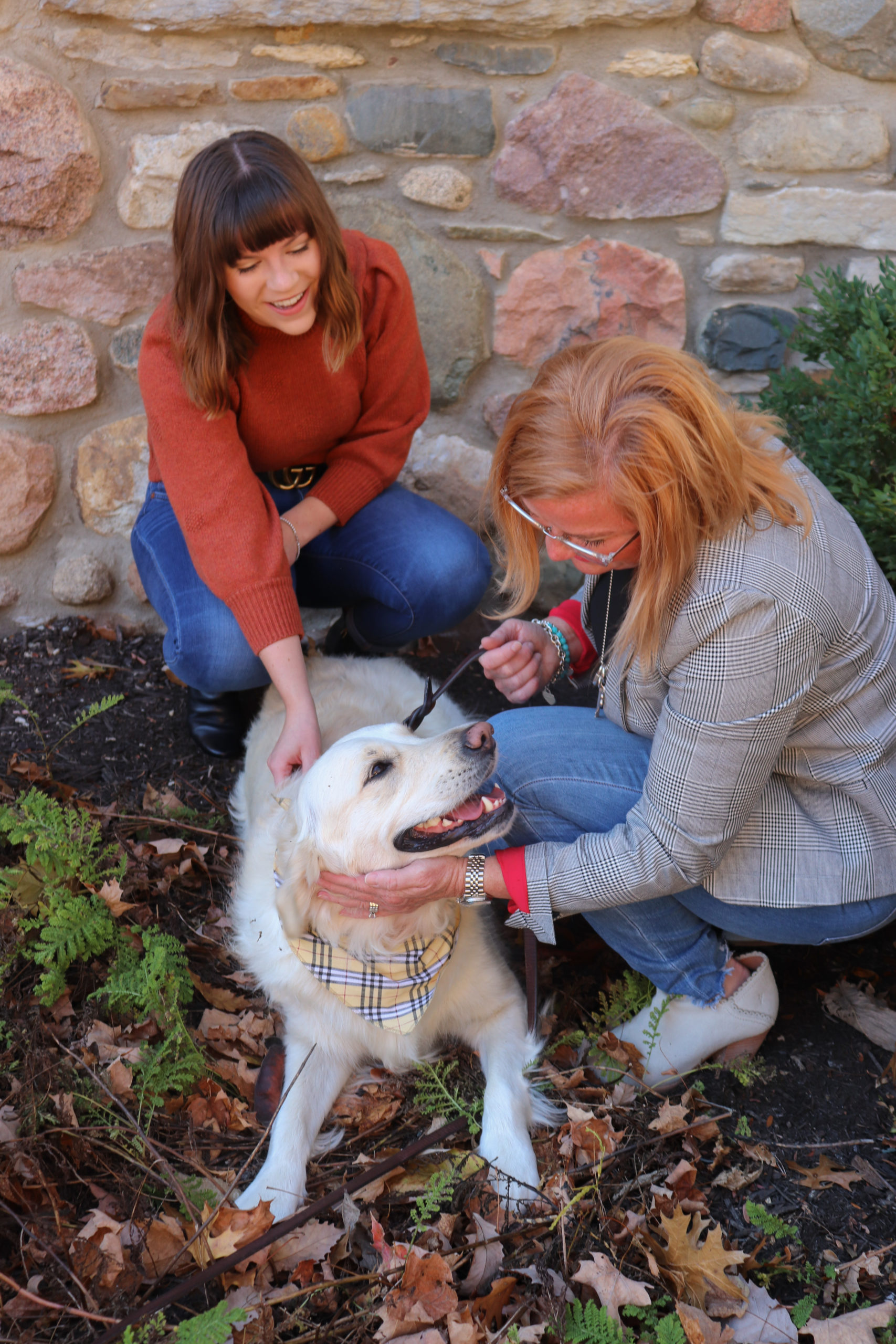 two women kneeling down and petting their dog