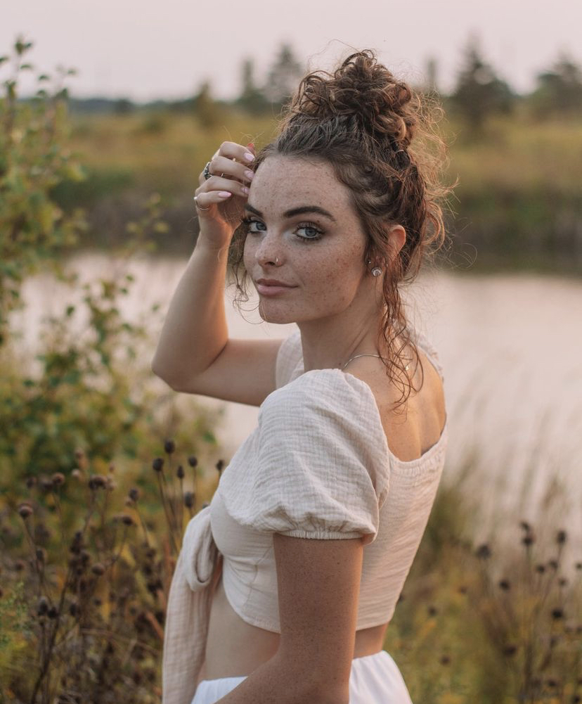 a photo of a girl standing in front of a pond
