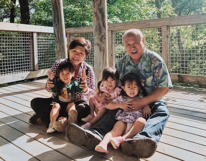 two grandparents sitting and holding their grandkids in their lap