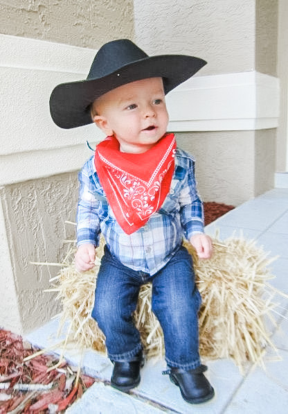 a little kid dressed as a cowboy sitting on hay