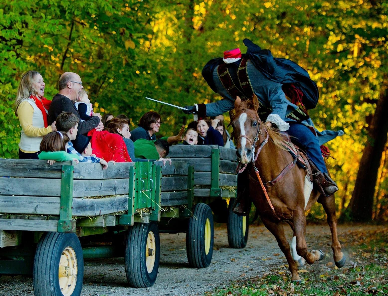 a photo of people on a wagon being chased by the headless horseman at conner prairie