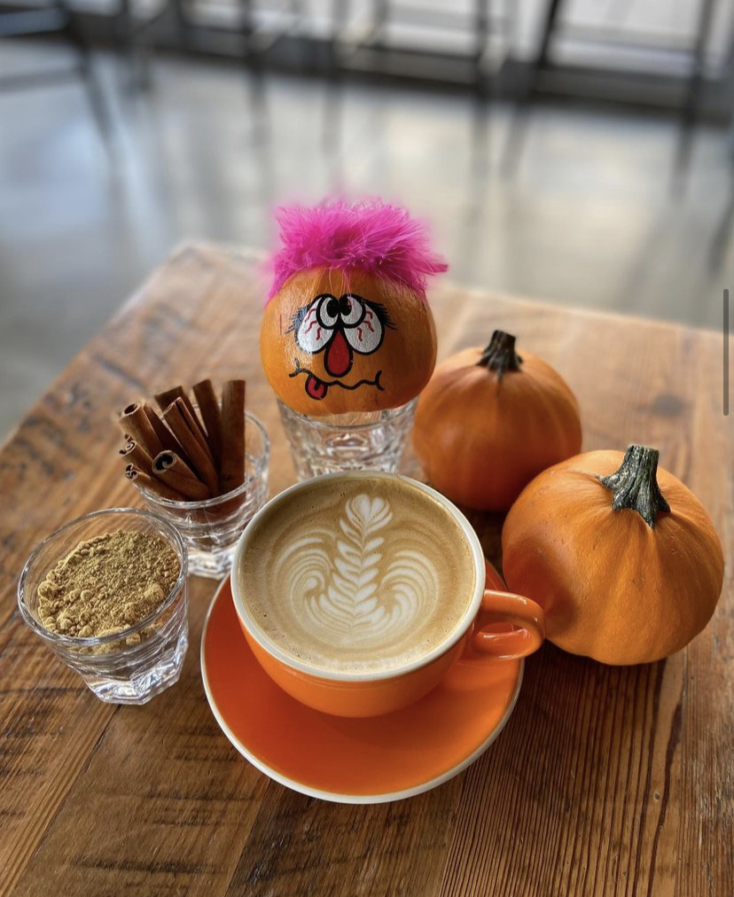 a cup of coffee surrounded by pumpkins