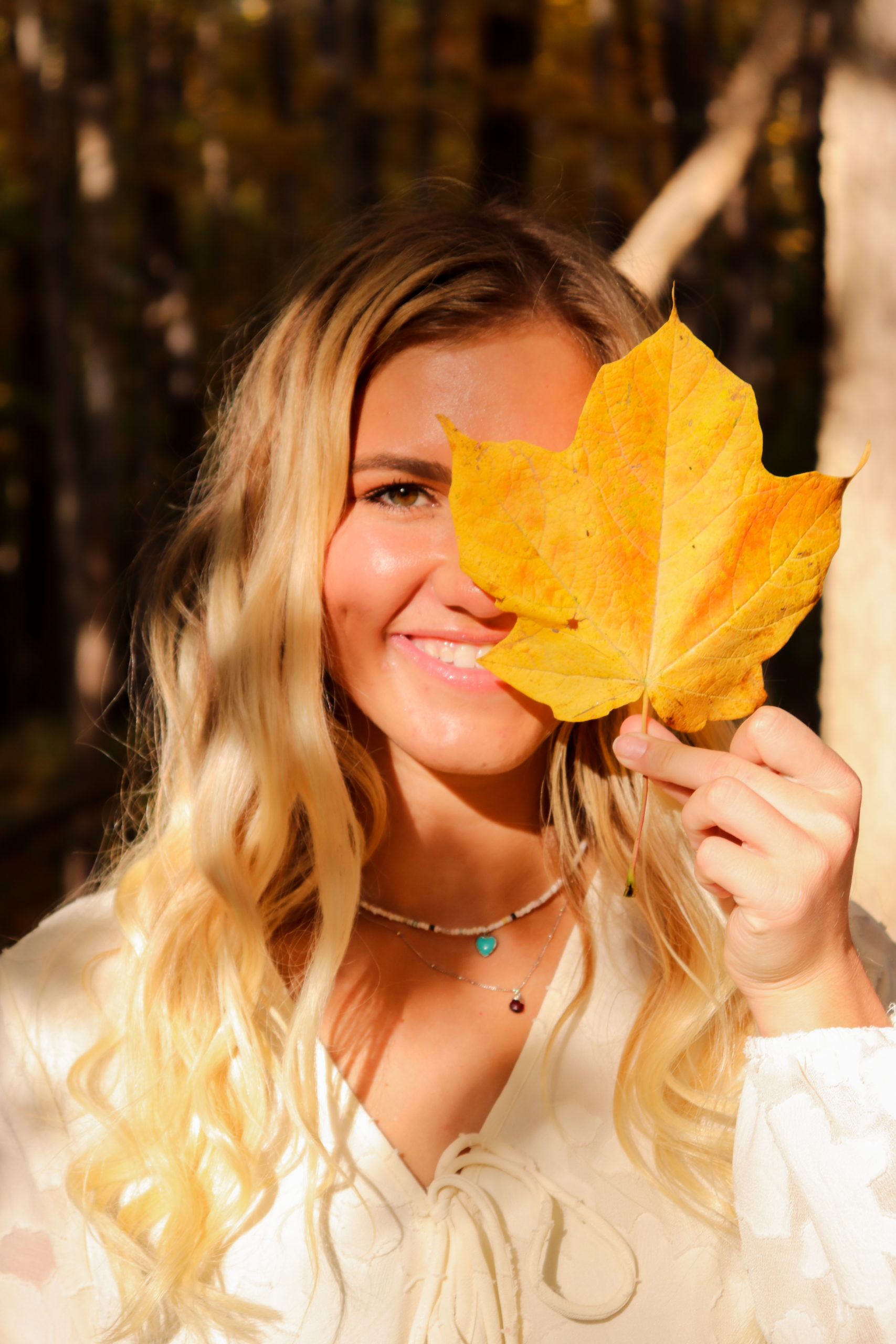 a close up of a girl holding a leaf on one half of her face